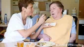 An elderly woman is pictured as she is fed by her female caregiver Photo: Tobias Kleinschmidt dpa/lsw