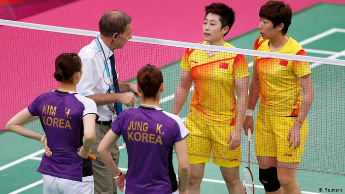 An official (2nd L) speaks to players from China and South Korea during their women's doubles group play stage Group A badminton match during the London 2012 Olympic Games