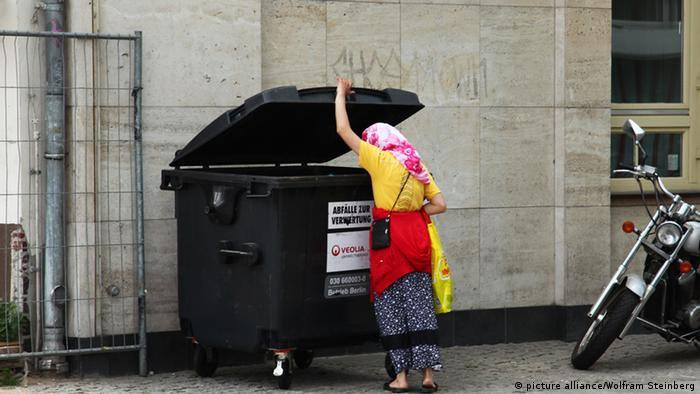 A woman peers into a dumpster (Photo: Wolfram Steinberg)