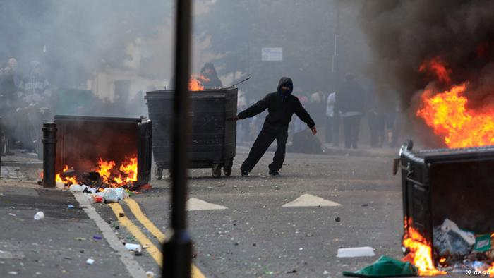 A masked youth pulls a burning garbage bin set on fire by rioters in Hackney, east London, Monday Aug. 8, 2011
