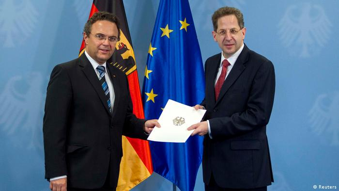 German Interior Minister Hans-Peter Friedrich (L) hands the letter of appointment to the new president of Germany's intelligence agency, the Verfassungsschutz, Hans-Georg Maassen in Berlin, August 1, 2012.