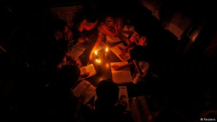 A teacher (C, top) conducts a lesson for students in the light of kerosene lamps and a candle during a power-cut inside a house in Kolkata July 31, 2012. (REUTERS/Rupak De Chowdhuri)