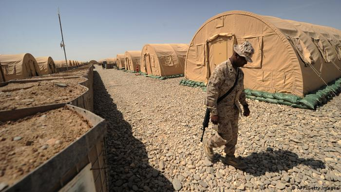 A US marine from Regimental Combat Team-8 walks between accommodation tents at Forward Operating Base Delaram in Helmand province, southern Afghanistan on April 4, 2011. Around 140,000 foreign troops are deployed in Afghanistan within the UN-mandated, NATO-led, International Security Assistance Force (ISAF) and the US-led coalition Operation Enduring Freedom, which overthrew the Taliban in late 2001. AFP PHOTO/Peter PARKS (Photo credit should read PETER PARKS/AFP/Getty Images)