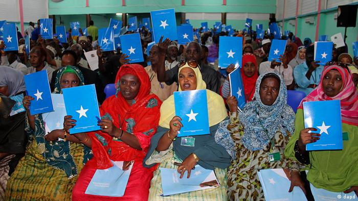 In this photo of Wednesday July 25, 2012, Somalia's constituency assembly members hold up copies of the proposed new constitution during the beginning of a nine-day meeting on Wednesday to examine, debate and vote on the proposed new constitution, in Mogadishu, Somalia. Somali leaders are debating a new constitution that protects the right to abortion to save the life of the mother and bans the circumcision of girls. (Foto:Farah Abdi Warsameh/AP/dapd)