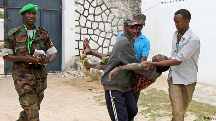 Somali police men carry an injured Somali soldier in Mogadishu Wednesday Aug.1, 2012 . The soldier was injured after two suicide bombers who were trying to blow up the constituent assembly venue were shot dead by security forces police said.(Foto:Farah Abdi Warsameh/AP/dapd)