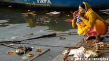 Eine Pilgerin hockt auf den Ghats (Steinstufen), die in den Ganges führen, in Varanasi (indischer Bundesstaat Uttar Pradesh) und verrichtet ihre Gebete und rituelle Waschungen, aufgenommen am 04.03.2011. Varanasi zählt zu den heiligsten Städten am Ufer des Ganges und gilt als Stadt des Gottes Shiva. Foto: Karlheinz Schindler pixel