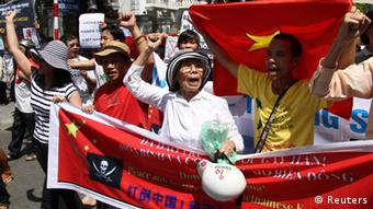Protesters hold banners while chanting slogans during an anti-China protest along a street in Hanoi