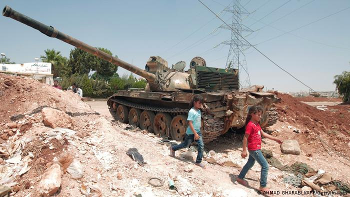 Two children walk past a tank said to have been captured by rebels near Aleppo