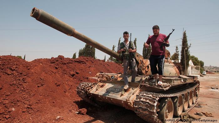 Syrian rebel fighters stand on top of a government tank