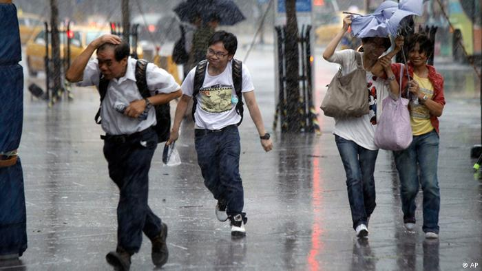 Tourists brave winds and rain from the approaching Typhoon Saola in Taipei, Taiwan, Wednesday, Aug. 1, 2012.