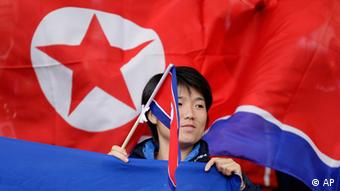 A North Korea supporter waves a flag before the team's group G women's soccer match against the United States at the London 2012 Summer Olympics, Tuesday, July 31, 2012 at Old Trafford Stadium in Manchester, England. (Foto:Jon Super/AP/dapd)