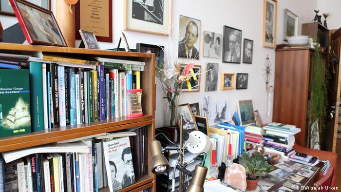 Bücherregal mit vielen Büchern und ein Schreibtisch, auf dem Bücher und Papiere liegen.