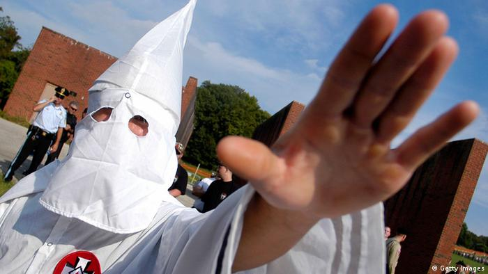 A Ku Klux Klan member in a white hood holds out his arm
