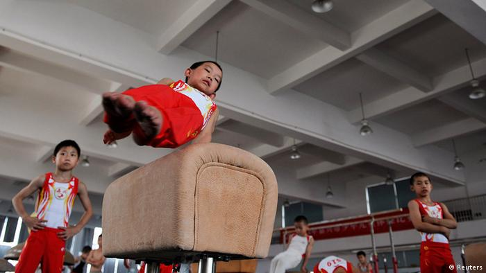 A young gymnast (front) practices on a pommel horse during a training session at a local juvenile sports school in Jiaxing, Zhejiang province July 10, 2012. REUTERS/Stringer (CHINA - Tags: EDUCATION SPORT SOCIETY GYMNASTICS) CHINA OUT. NO COMMERCIAL OR EDITORIAL SALES IN CHINA