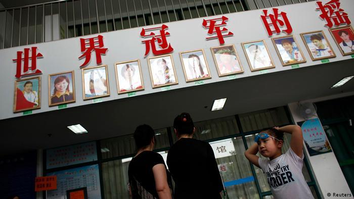 A girl waits outside the Chen Jinglun Sports School Natatorium in Hangzhou August 2, 2012,  where Chinese Olympic swimmer Ye Shiwen trained when she was young. At the Chen Jinglun Sports School in the picturesque city of Hangzhou, the slogan