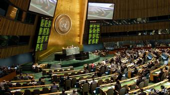 A hand is shown on a video screen, pushing a button to The United Nations General Assembly