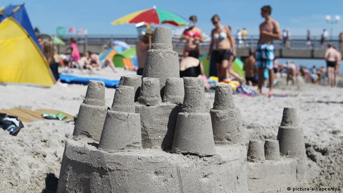 Eine Sandburg am Strand, im Hintergrund Badegäste