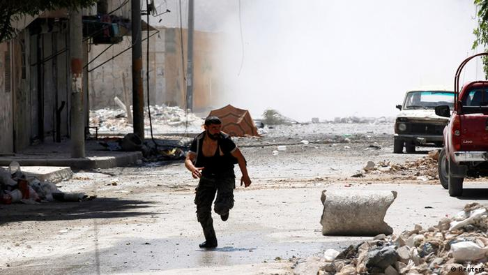 A man runs for cover during clashes between Free Syrian Army fighters and Syrian Army soldiers in the Salah al-Din neighborhood of central Aleppo August 4, 2012. REUTERS/Goran Tomasevic (SYRIA - Tags: CIVIL UNREST POLITICS)