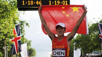 China's Chen Ding celebrates while holding his national flag after he won the men's 20k race walk during the London 2012 Olympic Games at The Mall August 4, 2012. Ding, 19, set a new Olympic record with a time of 1:18:46, finishing 11 seconds ahead of Guatemala's Erick Barrondo and Chinese compatriot Wang Zhen, who took silver and bronze respectively.