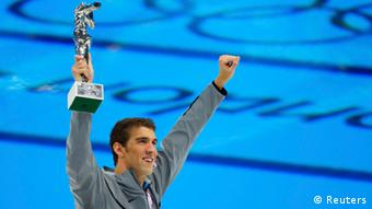 Michael Phelps of the U.S. holds up his award recognising him as the most decorated Olympian, during the London 2012 Olympic Games at the Aquatics Centre August 4, 2012. Phelps ended his incredible Olympic career on the perfect note on Saturday, winning his 18th gold medal for the United States in the men's medley relay, the last time he will swim a competitive race. REUTERS/Brian Snyder (BRITAIN - Tags: SPORT OLYMPICS SPORT SWIMMING TPX IMAGES OF THE DAY)