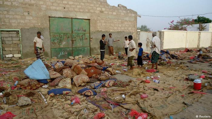 Locals in the Yemen city of Jaar clear wander through the site of a suicide attack that killed at least 45 people