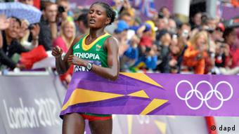 Ethiopia's Tiki Gelana crosses the finish lline to win gold in the women's marathon at the 2012 Summer Olympics on, Sunday, Aug. 5, 2012 in London.