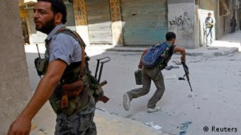 A Free Syrian Army fighter runs across a street dodging Syrian Army bullets in the Salah al- Din neighbourhood of central Aleppo August 5, 2012. REUTERS/Goran Tomasevic (SYRIA - Tags: CIVIL UNREST POLITICS TPX IMAGES OF THE DAY)