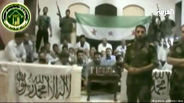A grainy picture taken from a television video shows a nondescript room with a green white and black flag and militant-looking men looking toward the camera.