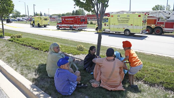 Bystanders sit in the shade at the scene of the shooting