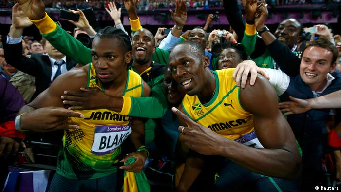 Jamaica's Usain Bolt and Yohan Blake (L) celebrate with supporters after the men's 100m final during the London 2012 Olympic Games at the Olympic Stadium August 5, 2012. Bolt came first ahead of Blake who finished second and Justin Gatlin of the U.S. who placed third. REUTERS/Kai Pfaffenbach (BRITAIN - Tags: SPORT ATHLETICS OLYMPICS)