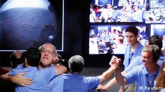 *****ACHTUNG SCHLECHTE QUALITÄT**** Image shot off a video screen from NASA TV shows members of the Mars Science Laboratory (MSL) team celebrating inside the Spaceflight Operations Facility for NASA's Mars Science Laboratory Curiosity rover at Jet Propulsion Laboratory after receiving the first few images from the Curiosity rover, in Pasadena, California August 5, 2012. Mission controllers at the Jet Propulsion Laboratory said they received signals relayed by a Martian orbiter confirming that the rover had survived a make-or-break descent and landing attempt to touch down as planned inside a vast impact crater. REUTERS/Courtesy NASA TV/Handout (UNITED STATES - Tags: SCIENCE TECHNOLOGY) FOR EDITORIAL USE ONLY. NOT FOR SALE FOR MARKETING OR ADVERTISING CAMPAIGNS. THIS IMAGE HAS BEEN SUPPLIED BY A THIRD PARTY. IT IS DISTRIBUTED, EXACTLY AS RECEIVED BY REUTERS, AS A SERVICE TO CLIENTS