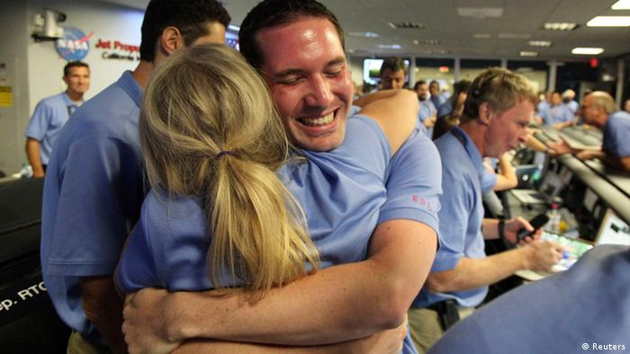 A NASA scientist hugs a colleague in celebration, inside the Spaceflight Operations Facility for NASA's Mars Science Laboratory Curiosity rover in Pasadena, California.