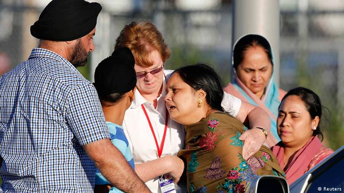 A distraught women is helped to a car outside of the Sikh temple in Oak Creek, Wisconsin August 5, 2012. A shooting during Sunday services at the temple left at least seven people dead, including a gunman, and at least three critically wounded, police and hospital officials said. REUTERS/Tom Lynn (UNITED STATES - Tags: CRIME LAW TPX IMAGES OF THE DAY)