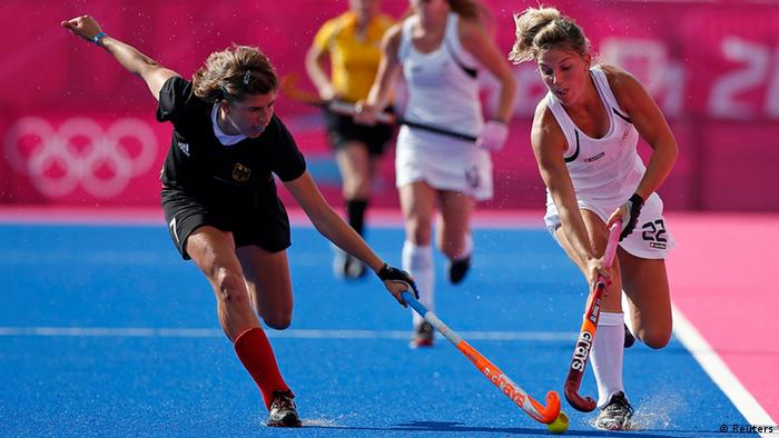 New Zealand's Gemma Flynn fights for the ball with Germany's Natascha Keller (L) during their Women's group B hockey match at Riverbank Arena at the London 2012 Olympic Games August 6, 2012.