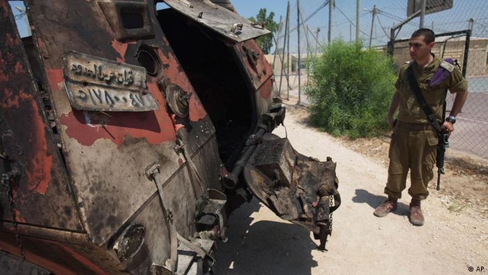 An Israeli soldier examines the wreckage of an Egyptian military vehicle after militants burst it through a security fence into Israel from Egypt, at an Israeli military base along the border with Egypt, southern Israel, Monday, Aug. 6, 2012. Officials say Egypt has deployed at least two helicopter gunships to the Sinai Peninsula in the hunt for militants behind the killing of 16 Egyptian soldiers at a checkpoint along the border with Israel. Suspected Islamists on Sunday evening attacked the Egyptian checkpoint, killed the troops, then stole two of their vehicles and burst through a security fence into Israel. Israeli aircraft then halted their assault. (Foto:Ariel Schalit/AP/dapd)