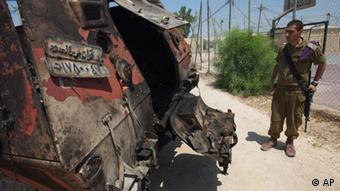 An Israeli soldier examines the wreckage of an Egyptian military vehicle after militants burst it through a security fence into Israel from Egypt, at an Israeli military base along the border with Egypt, southern Israel, Monday, Aug. 6, 2012(Photo:Ariel Schalit/AP/dapd)