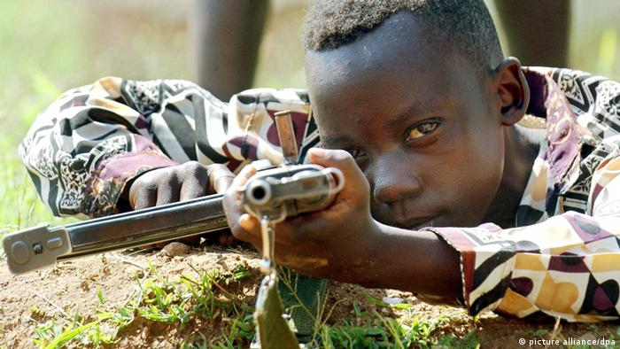 Ten-year-old Congolese child soldier with firearm at shooting practice. Photo: Maurizio Gambarini dpa