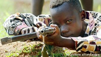 Um soldado de 10 anos de idade, da milícia armada União dos Patriotas Congoleses, em treinamento no ano de 2003, nas proximidades de Bunia no Congo