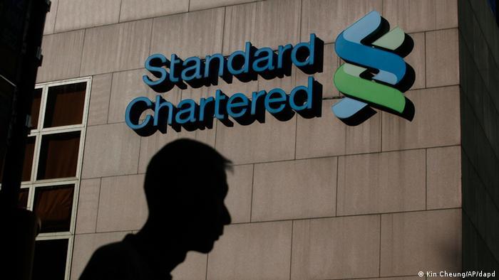 Логотип Standard Chartered Bank на стіні, повз який проходить чоловік