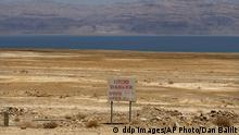 In this photo taken Thursday, May 28, 2009, a warning sign is seen near the Dead Sea coast. Geologist Eli Raz says the sinkholes phenomenon, underground craters that can burrow to the surface in an instant, sucking in whatever lies above, stems from a dire water shortage, compounded in recent years by a growing population and robust tourism and chemical industries. (ddp images/AP Photo/Dan Balilty) German industrial conglomerate Siemens AG said Monday June 22, 2009 that it expects to garner some 15 billion euro (US$20.9 billion) worldwide in new orders because of more government-backed mandates aimed at reducing energy consumption