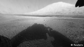 An image taken by NASA's Mars science rover Curiosity shows what lies ahead for the rover --- its main science target, Mount Sharp, in this handout image released by NASA August 6, 2012. The rover's shadow can be seen in the foreground, and the dark bands beyond are dunes. Rising up in the distance is the the distance is the highest peak Mount Sharp at a height of about 3.4 miles, taller than Mt. Whitney in California. The Curiosity team hopes to drive the rover to the mountain to investigate its lower layers, which scientists think hold clues to past environmental change. This image was captured by the rover's front left Hazard-Avoidance camera at full resolution shortly after it landed. It has been linearized to remove the distorted appearance that results from its fisheye lens. REUTERS/NASA-JPL-Calthech/Handout (UNITED STATES - Tags: SCIENCE TECHNOLOGY) THIS IMAGE HAS BEEN SUPPLIED BY A THIRD PARTY. IT IS DISTRIBUTED, EXACTLY AS RECEIVED BY REUTERS, AS A SERVICE TO CLIENTS. FOR EDITORIAL USE ONLY. NOT FOR SALE FOR MARKETING OR ADVERTISING CAMPAIGNS