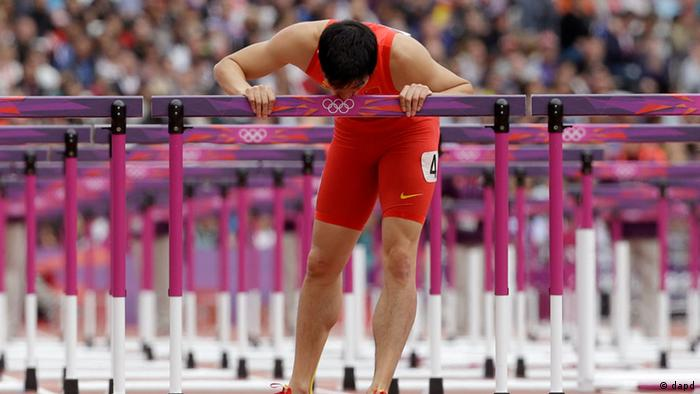 China's Liu Xiang kisses his hurdle after falling in a men's 110-meter hurdles heat during the athletics in the Olympic Stadium at the 2012 Summer Olympics, London, Tuesday, Aug. 7, 2012.