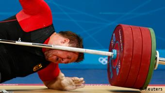 Germany's Matthias Steiner is struck by his falling weight after he dropped it during the men's +105kg Group A snatch weightlifting competition at the ExCel venue during the London 2012 Olympic Games August 7, 2012. REUTERS/Grigory Dukor (BRITAIN - Tags: OLYMPICS SPORT WEIGHTLIFTING TPX IMAGES OF THE DAY)