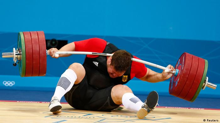 Germany's Matthias Steiner is injured while his weights fall during the men's +105kg Group A snatch weightlifting competition at the ExCel venue during the London 2012 Olympic Games August 7, 2012. REUTERS/Grigory Dukor (BRITAIN - Tags: OLYMPICS SPORT WEIGHTLIFTING TPX IMAGES OF THE DAY)