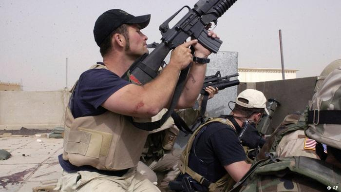 ** FILE ** In a file photo Plainclothes contractors working for Blackwater USA take part in a firefight as Iraqi demonstrators loyal to Muqtada Al Sadr attempt to advance on a facility being defended by U.S. and Spanish soldiers, Sunday, April 4, 2004 in the Iraqi city of Najaf, The State Department may phase out or limit the use of private security guards in Iraq, which could mean canceling Blackwater USA's contract or awarding it to another company in line with an Iraqi government demand, The Associated Press has learned. (AP Photo/Gervasio Sanchez)e