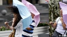 In this photo released by China's Xinhua News Agency, people walk in a rainstorm brought by Typhoon Haikui in Shanghai, China, Wednesday, Aug. 8, 2012. The typhoon slammed into eastern Zhejiang province early Wednesday, packing winds up to 150 kilometers (90 miles) per hour and triggering flooding. (Foto:Xinhua, Pei Xin/AP/dapd) NO SALES