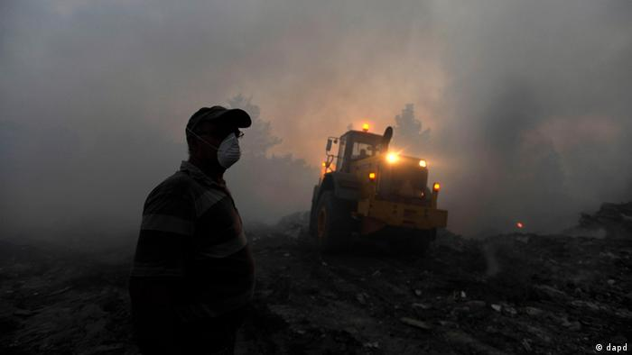 A bulldozer works to extinguish a fire near the town of Kassandria in Halkidiki peninsula, northern Greece.