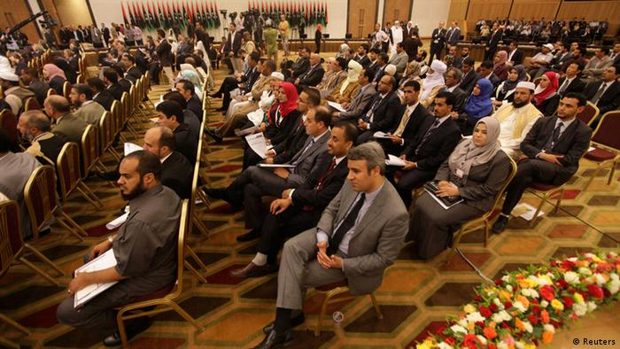 People sit during the National Transitional Council handover ceremony of power to the national congress in Tripoli