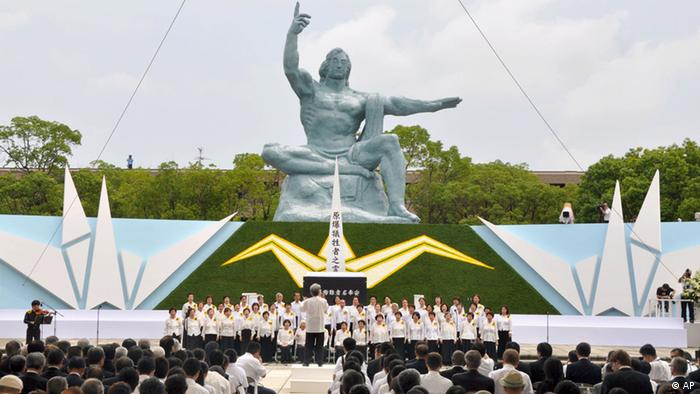 A ceremony is held in front of the Statue of Peace at Nagasaki Peace Park