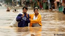 A couple wades through a flooded street as they evacuate from their home in Marikina city, Metro Manila August 9, 2012. Large parts of Manila were still swamped in floods on Thursday, after continuous rains pounded the capital overnight. REUTERS/Tim Chong (PHILIPPINES - Tags: DISASTER ENVIRONMENT)